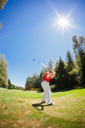 Male golf player performs a swing. Summer outdoor sport and wealthy class concept. photo