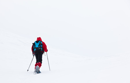 outdoorsman: A young boy is walking through the snow in mountain with snowshoes and ski poles. Winter season, cloudy and cold day. Red jacket and blue backpack.