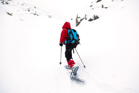ski walking: A young boy is walking through the snow in mountain with snowshoes and ski poles. Winter season, cloudy and cold day. Red jacket and blue backpack.