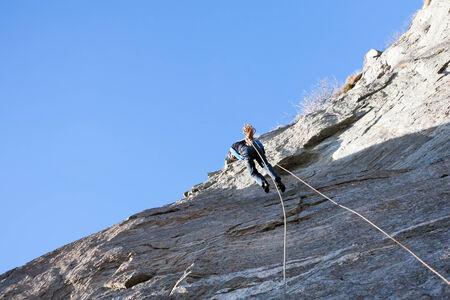 abseiling: A rock climber abseiling off a climb. Italian Alps.
