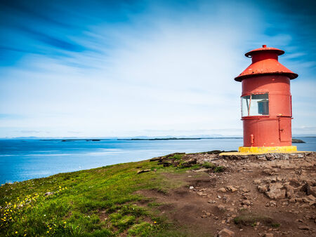 navigation aid: Little red lighthouse situated at the top of a cape over a sunny seascape  Related concept  navigation, help, aid, guide  Stykkisholmur, Iceland, Europe