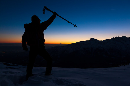 reached: At sunset a man stands on a snowy peak expressing his joy for have reached the top of a mountain peak  Concept  adventure, achievement, sport