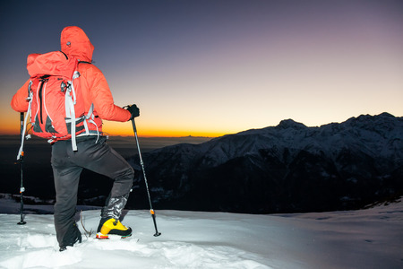 Winter hiking  man stands on a snowy ridge looking at the sunset  South Alps mountain  landscape  Italy, Europe  photo
