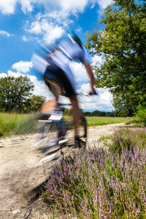 Cyclist in blurred motion riding on a rural road through green spring meadow photo