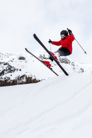 aosta: Male kid performs a high jump with the ski  Winter season, red jacket  Valle d