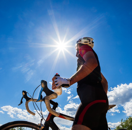 isotonic: Cyclist resting and drinking isotonic drink  Backlight, sunny summer day  Stock Photo