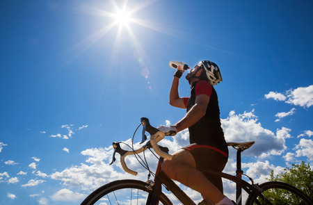 cycling   helmet: Cyclist resting and drinking isotonic drink  Backlight, sunny summer day  Stock Photo