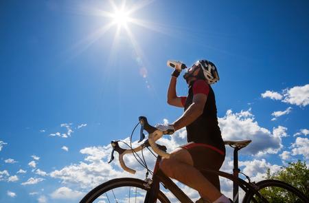 Radfahrer Ruhe-und isotonisches Getränk trinkt Hintergrundbeleuchtung, sonnigen Sommertag