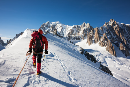 Mountaneer climbs a snowy ridge in Mont Blanc, France  Enterprise, diligence, team work  mountaneering concepts  photo