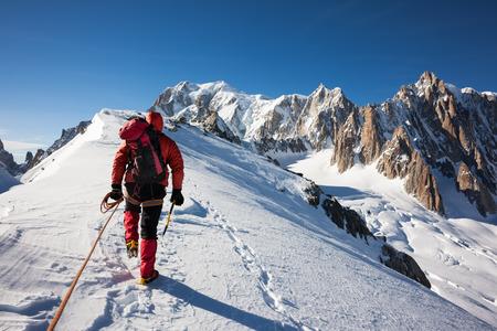 klimmer: MOUNTANEER klimt een besneeuwde bergkam in de Mont Blanc, Frankrijk Enterprise, toewijding, teamwork bergsport concepten
