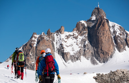 The Aiguille du Midi peak; in foreground a defocused group of mountaineers  Mont Blanc massif, Chamonix, France, Europe  Stock Photo
