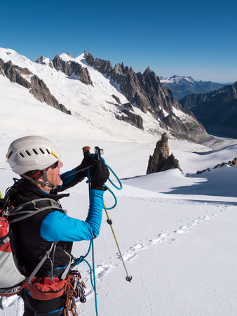 Mountaineer taking picture with a camera in the mountains  Mont Blanc Glacier, Chamonix, France, Europe  photo