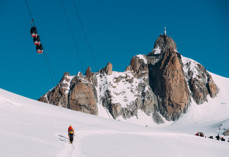 The Aiguille du Midi peak with Panoramic Mont-Blanc cable car; in foreground a group of mountaineers  Mont Blanc massif, Chamonix, France, Europe