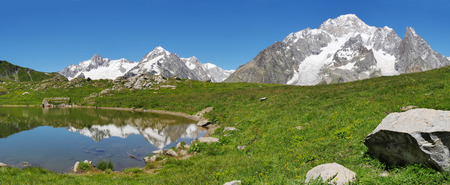 veny: The south face of Mont Blanc (italian side), from the Vesses lake in Val Veny valley along the famous Tour du Mont Blanc trail. Courmayer, Valle dAosta, Italy. Stock Photo