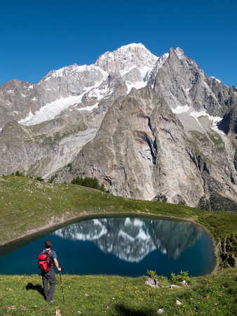 aosta: A hiker takes a rest looking at Mont Blanc, the highest peak in Europe. Val Veny, Courmayer, Italy, Europe.