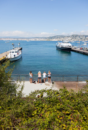 rins: A group of young blonde girls waiting for their ferry on the dock  Île Sainte-Marguerite  Lérins Islands  - Cannes, French Riviera, Europe  Stock Photo