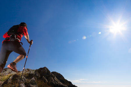 trekker: Skyrunner runs uphill along a mountain trail. Rear way, caucasian young man. Sunny summer day. West Alps, Europe.
