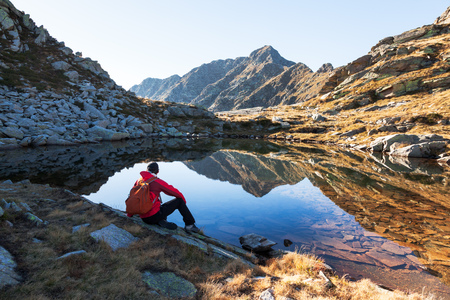 expedition: Male hiker takes a rest sitting next a mountain lake. Autumn sunny day. West italian Alps, Oropa, Piemonte, Italy, Europe.