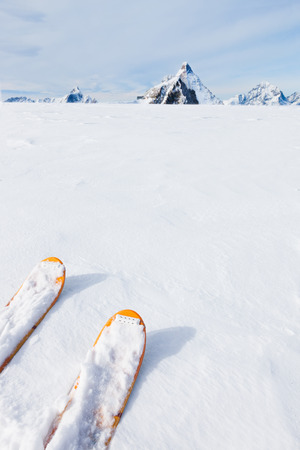 verve: Ski tips, snow field and mountain landscape in background (the Matterhorn, Zermatt, Switzerland). Large white copy space. Stock Photo
