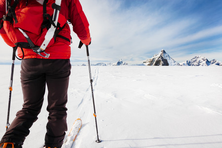 expedition: Mountaineer exploring a glacier with the skis during a high-altitude winter expedition in the european Alps. In background the Matterhorn, Zermatt, Switzerland, Europe. Stock Photo