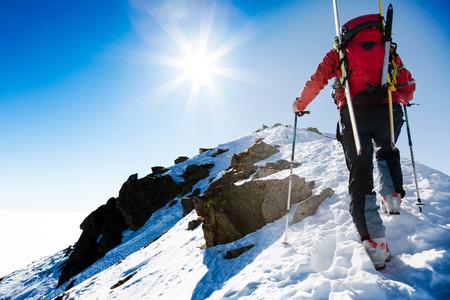 climbing: Mountaineer caminando a lo largo de una cresta de nieve empinada con los esqu�s en la mochila.
