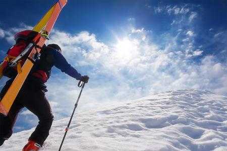 Ski bergbeklimmer omhoog langs een steile besneeuwde bergkam met de ski's in de rugzak. In de achtergrond een dramatische hemel met een glanzende heldere zon. Begrippen: avontuur, prestatie, moed, vastberadenheid, zelfrealisatie, gevaarlijke activiteit, extreme sport, winter
