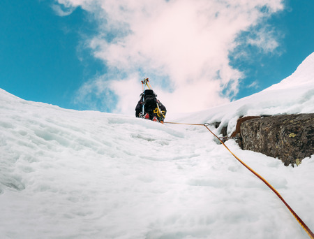 ice axe: Ice climbing: mountaineer on a mixed route of snow and rock during the winter. Western Alps, Italy, Europe. Stock Photo