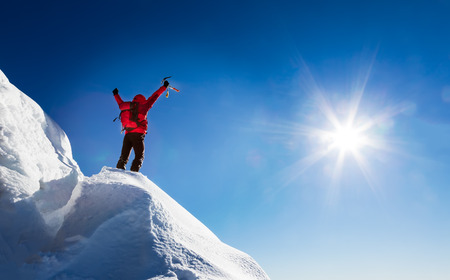 achievement: Mountaineer celebrates the conquest of the summit. Concepts: victory, success, achievement, triumph.