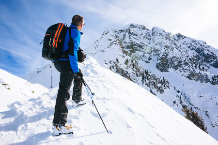 snow white: Winter vacation: mountaineer takes a rest looking at the mountain panorama. In background a snowy peak in western Alps. Val dAosta, Italy, Europe. Stock Photo