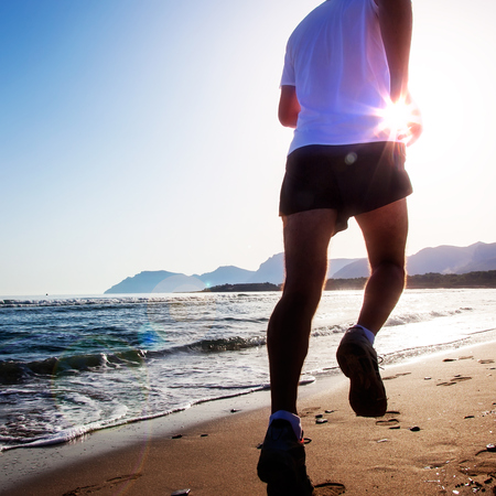running man: Man running at sunset on a sandy beach in a sunny day. Caucasian male, white shirt, summer season, spanish mediterranean coast. Large copy-space in the sky. Full released.