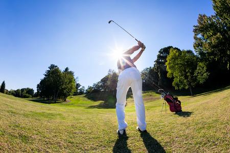 Golfsport: mannelijke blanke golfer slaat een shoot van de fairway. Zomer, zonnige dag. Stockfoto