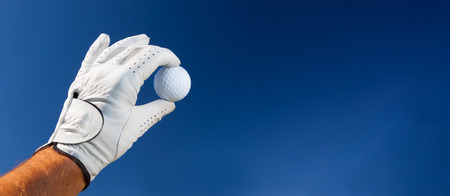 golf glove: Hand wearing golf glove holding a white golf ball over a deep blue sky. Large copy-space at the right for title and text.