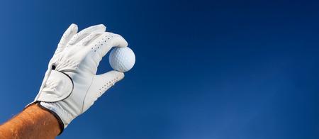 guantes: Mano usando guante de golf la celebración de una pelota de golf blanco sobre un cielo azul profundo. Gran copia de espacio a la derecha para el título y el texto.
