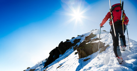 summits: Mountaineer walking up along a steep snowy ridge with the skis in the backpack. In background a dramatic sky with a shiny bright sun. Concepts: adventure, achievement, courage, determination, self-realization, dangerous activity, extreme sport, winter lei