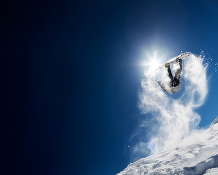 snowboard: Snowboarder making high jump in clear blue sky. Concept: fun, sport, courage, adventure, danger, extreme. Large copy space on the left side. Stock Photo