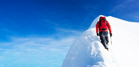 summits: Mountaineer arrive to the summit of a snowy peak. Concepts: determination, courage, effort, self-realization. Clear sky, sunny day, winter season. Large copy-space on the left. European Alps, Europe. Stock Photo
