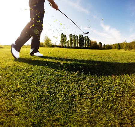 golf man: Golf swing on the course. Golfer performs a golf shot from the fairway. Sunny summer day. Concept: sport, relax, tourism, welfare. Stock Photo