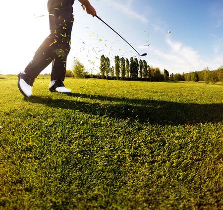 Swing de golf en el curso. Golfista realiza un tiro de golf desde la calle. Día soleado de verano. Concepto: el deporte, relax, el turismo, el bienestar. Foto de archivo