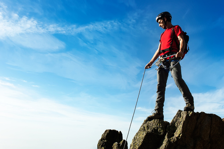 team cooperation: A climber helps his partner to reach the summit of a mountain peak. Concepts: cooperation, team work, guidance, aid, reliability, strength, perseverance.