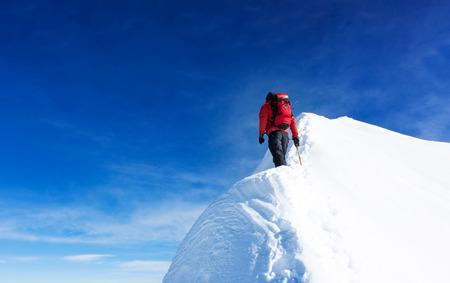 Alpinista alcanzar la cima de un pico nevado. Conceptos: determinación, valor, esfuerzo, la auto-realización. cielo despejado, día soleado, temporada de invierno. Gran espacio de copia a la izquierda. Alpes Europeos, Europa. Foto de archivo