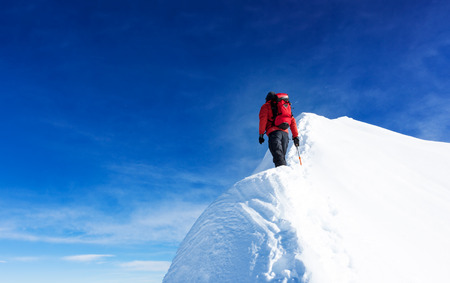 Mountaineer reach the summit of a snowy peak. Concepts: determination, courage, effort, self-realization. Clear sky, sunny day, winter season. Large copy-space on the left. European Alps, Europe. Stock Photo