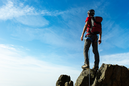 victory stand: Climber arrive on the summit of a mountain peak. Concepts: victory, success, achievement, triumph. Stock Photo