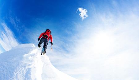 Mountaineer arriver au sommet d'un pic enneigé. Concepts: détermination, le courage, l'effort, la réalisation de soi. Journée ensoleillée d'hiver, Alpes européennes.