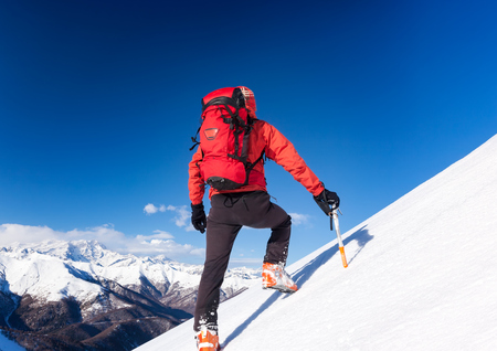alpinist: Climber walks up a snowy slope. Winter season, clear sky. In background the Monte Rosa massif, Italy, Europe.