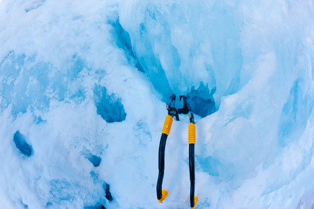 icefall: Two modern ice tools planted in the icefall during a pitch. Cogne (Val dAosta) - Italy. Stock Photo