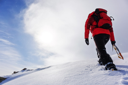 self realization: Mountaineer climbing a snowy peak in winter season. Concepts: determination, courage, effort, self-realization.