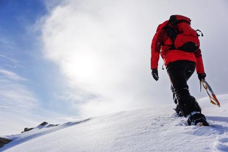 self realization: Mountaineer climbing a snowy peak in winter season. Concepts: determination, courage, effort, self-realization.