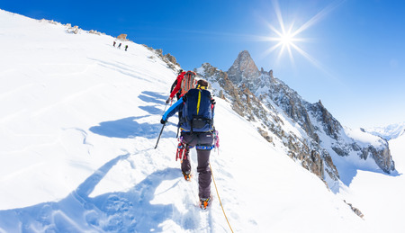 dent: Mountaineers climb a snowy peak. In background the famous peak Dent du Geant in the Mont Blanc Massif, the highest european mountain. The Alps, Chamonix, France, Europe.