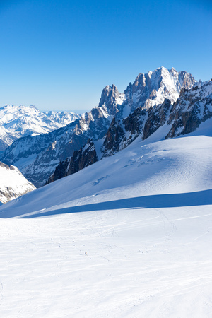 A lonely skier goes down along Valle Blanche, an offpiste run that links Italy to France. In background Aiguille Verte and the Drus peaks. Chamonix, France, Europe.