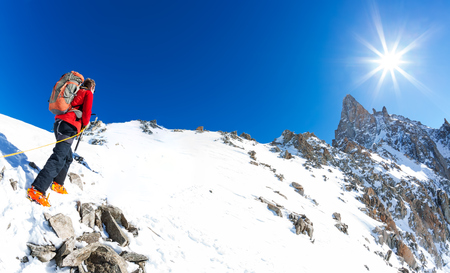 dent: Mountaineer climbs a snowy peak. In background the famous peak Dent du Geant in the Mont Blanc Massif, the highest european mountain. The Alps, Chamonix, France, Europe.